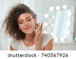 smiling woman applying serum on ... | Shutterstock . vector #740567926