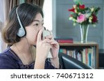 Small photo of Close up beautiful young asian woman short hair listening music in living room at home