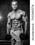 Small photo of Handsome young muscular Caucasian man of model appearance working out training pumping up abdominal muscles abs sixpacks in the gym gaining weight and poses fitness and bodybuilding concept