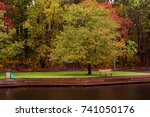 a walkway and park bench by the ... | Shutterstock . vector #741050176
