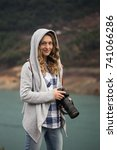 Small photo of Blonde woman photographer wearing jeans, checked shirt and gray hoodie holding long focal