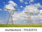 Super wide angle photograph of a row of power lines against a blue cloudy sky. - stock photo