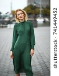 Small photo of Woman in green dress looks stunning posing against the wind