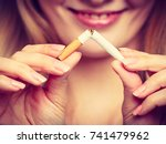Small photo of Smilling woman breake down cigarette. Winning with addicted nicotine problems, stop smoking. Quitting from addiction concept. On blue