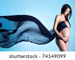 Glamour and style of young pregnant woman with blue material on the blue background - stock photo