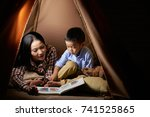 mother reading book to her... | Shutterstock . vector #741525865