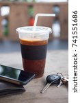Small photo of Ice of americano or black coffee with men wallet and car key