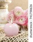 Small photo of Romantic candle holder and bouquet of pink ranunculus flowers.
