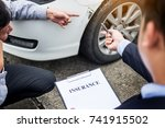 Small photo of Insurance agent writing on clipboard while examining car after accident claim being assessed and processed