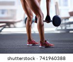 sexy woman lifting barbell at... | Shutterstock . vector #741960388