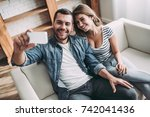 happy couple is sitting on sofa ... | Shutterstock . vector #742041436