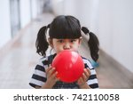 Little Girl Blowing Up Red...