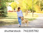 Stock photo mature woman walking her dog in park 742205782