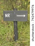 Small photo of Grey wooden sign with the abbreviated Dutch text number in white color