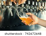 Stock photo hand of bartender pouring a large lager beer in tap 742672648