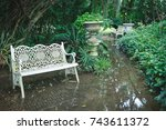 White chair in waterlogged outdoor garden, full of trees and bushes.