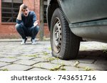 Small photo of Crouched Worried Young Man With Hand On Head Pointing At Punctured Car Tire