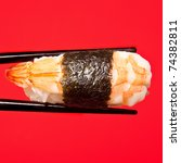 Prawn sushi being held in chopsticks. Photographed against a red studio background. - stock photo