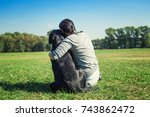 a woman with dog in the park. | Shutterstock . vector #743862472