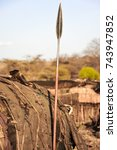 Small photo of Samburu, Kenya - traditional mud dwelling (manyatta) with tribal spear placed outside. The village is known as a kraal or boma, the spear is used for hunting, special ceremonies and as a symbol