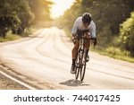 man ride a bicycle at sun set ... | Shutterstock . vector #744017425