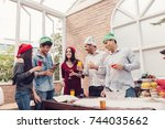 Small photo of Cheers to best friends! Top view of cheerful young people cheering with champagne flutes and looking happy while having party on the kitchen celebrating ,Christmas or New Year at home