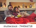 couple at home eating pop corns ... | Shutterstock . vector #744066718