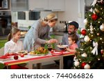 family together at decorated... | Shutterstock . vector #744066826