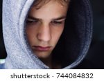 portrait of a serious teenage boy on a dark background, teenage  problem concept - stock photo