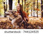 Stock photo young beautiful red haired girl in a fashionable orange sweater is walking with her dog in the park 744124525