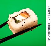 Salmon and cream cheese sushi roll being held in chopsticks. - stock photo