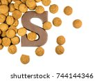 Small photo of Handful of thrown Pepernoten cookies with chocolate letter as Sinterklaas decoration on white background for dutch sinterklaasfeest holiday event on december 5th