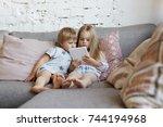 elder sister relaxing on couch... | Shutterstock . vector #744194968