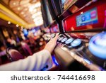 Casino Slot Video Games. Woman Playing Video Slot in the Casino. Hand on Betting Button Closeup Photo. - stock photo