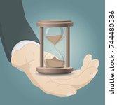 hand holding sandglass... | Shutterstock .eps vector #744480586