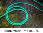 green water hose on  the wet... | Shutterstock . vector #744583876