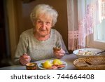 an elderly woman eats at home.   Shutterstock . vector #744664408