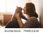 young woman playing with cat in ... | Shutterstock . vector #744811618