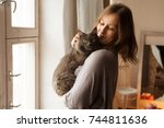Stock photo young woman playing with cat in home 744811636