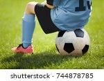 child sitting on soccer ball....   Shutterstock . vector #744878785