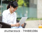 young woman using a tablet | Shutterstock . vector #744881086