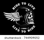 biker skull in helmet with wing.... | Shutterstock . vector #744909052