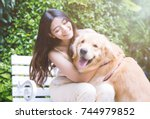 Stock photo portrait of woman with dog golden retriever in park with sunset out door 744979852