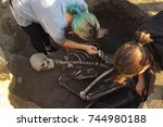 Small photo of Archaeological excavations. archaeologist with tools conducts research on human burial, skeleton, skull.