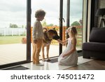 children caressing watch dog... | Shutterstock . vector #745011472