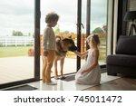 children caressing watch dog... | Shutterstock . vector #745011472