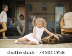 little girl playing with dog... | Shutterstock . vector #745011958