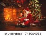 santa claus reads a book to a... | Shutterstock . vector #745064086