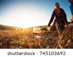 a glass of wine at sunset. a... | Shutterstock . vector #745103692