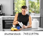 Small photo of Man preparing protein shake in kitchen